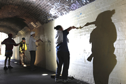 Young people engaged in community service programs such as graffiti removal